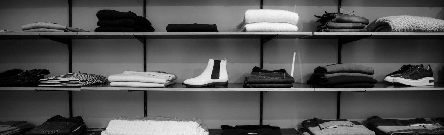 grayscale-photography-of-assorted-apparels-on-shelf-rack-1884581